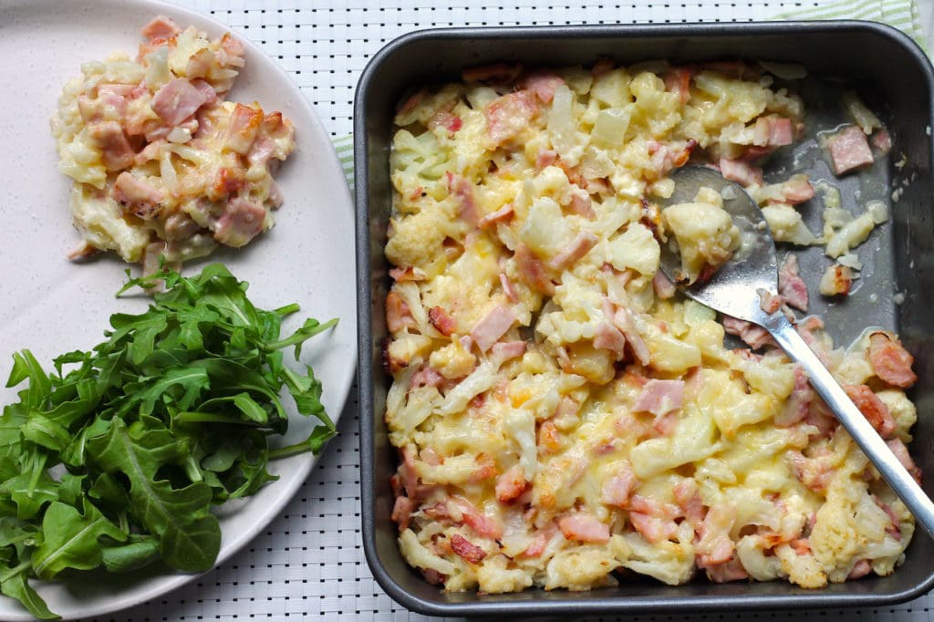 Keto Cauliflower Cheese Bake on a tray with green leafy vegetable on the side. Keto Cauliflower Cheese Bake recipe by Aussie Keto Queen