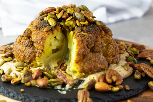 Vegetarian Keto Whole Roasted Cauliflower is bursting with Middle Eastern spices and so much flavour, plus a crunchy nutmix on top and a tasty tahini dressing. The ultimate vegetarian Keto main, or a fantastic side dish! #keto #ketorecipes #ketogenicdiet