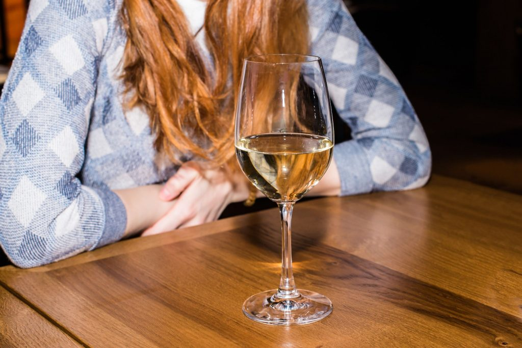 Can you drink Alcohol on Keto diet? If you're on the keto diet, then chances are you've been wondering if alcohol is good for your diet. Woman sitting with a glass of alcohol on the table