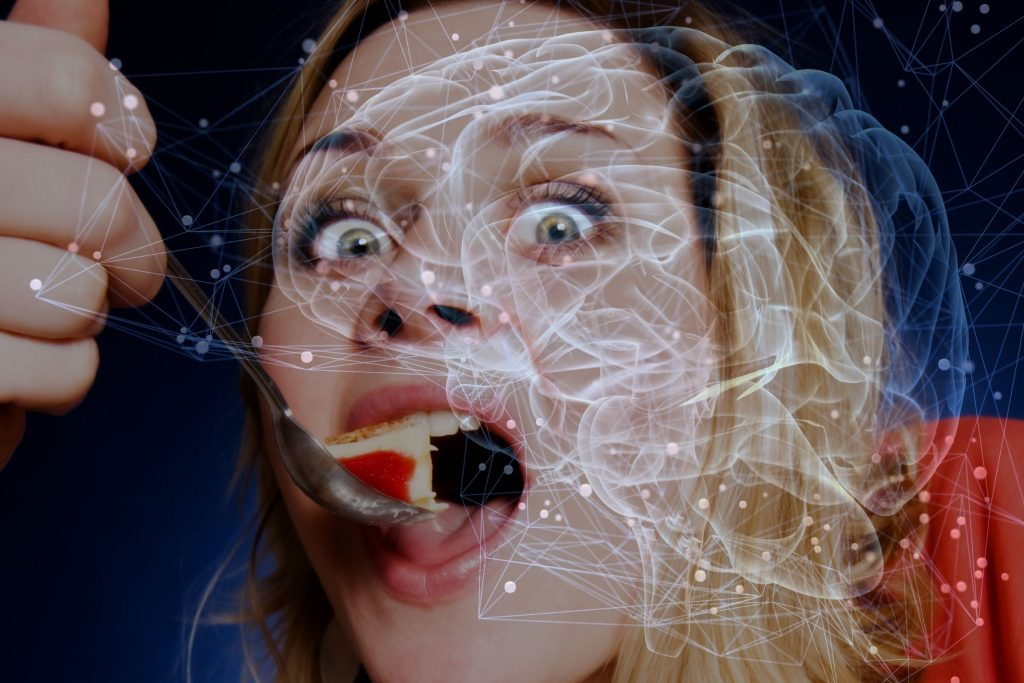 10 Tips for Cravings on the Ketogenic Diet: Why You Get Them & How to Stop.Body Cravings Vs. Brain Cravings. Picture of a woman putting food inside her mouth with abstract image of a brain overlay.