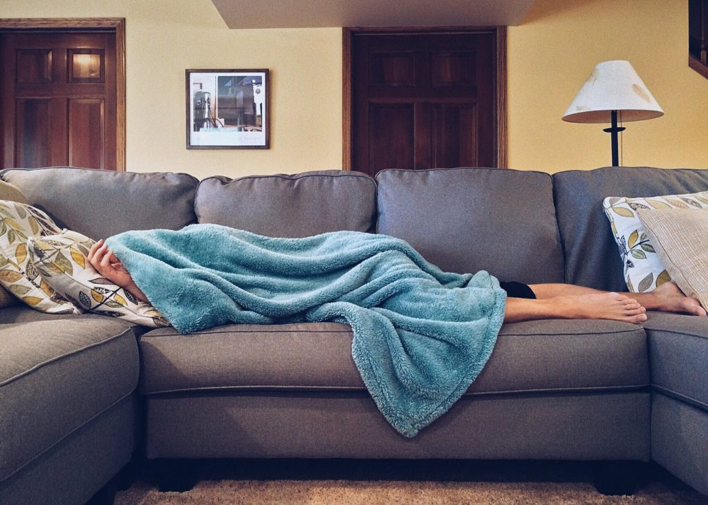 A person laying on the couch, covered with a blanket while they recover from a cold. Using Keto Bone broth to support your recovery can be key to getting back on track sooner! The benefits of bone broth are huge.