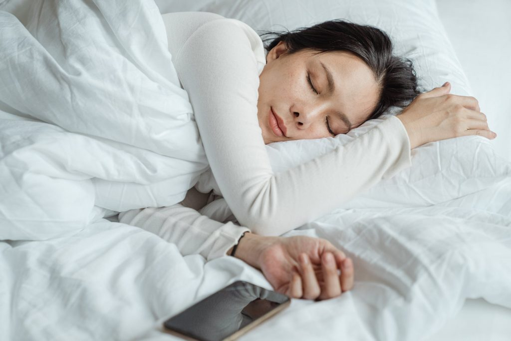 A woman sleeping soundly is shown, with improved sleep being a key benefit of bone broth on your keto diet. Bone Broth can help you relax, fall asleep faster and improve the overall quality of your sleep - essential for weight loss.
