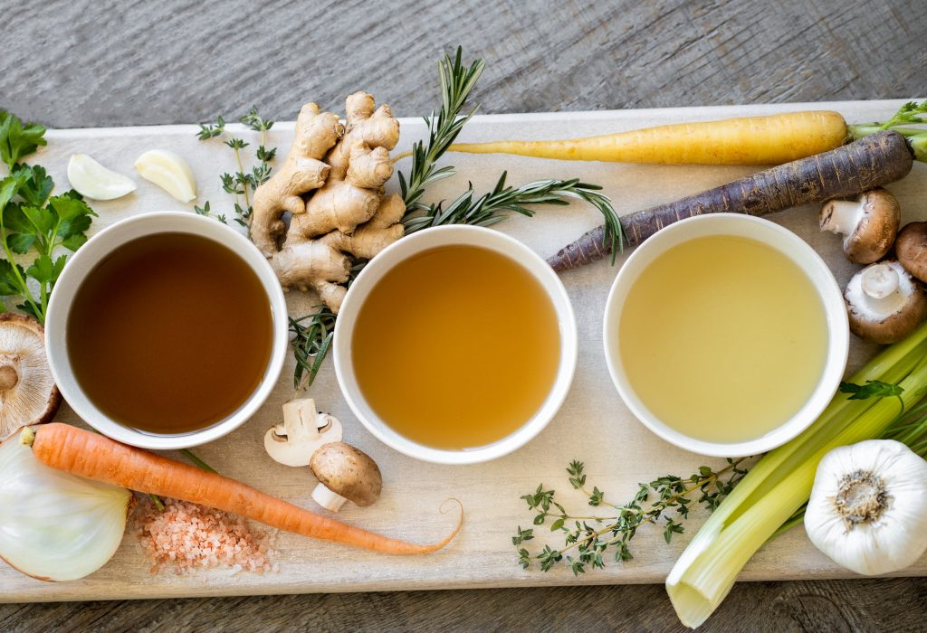 3 different coloured bone broths surrounded by their vegetables and ingredients. The benefits of chicken bone broth are amazing, and perfectly complement a Keto diet.